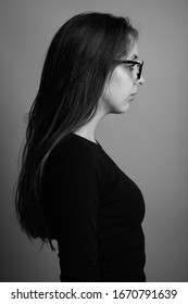 Portrait of young beautiful woman against gray background