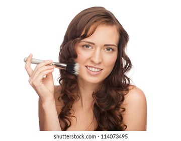 Portrait of young beautiful woman applying blusher on her face. Pretty woman applying makeup, isolated on white