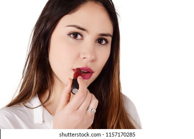Portrait of a young beautiful woman applying lipstick. Isolated white background.