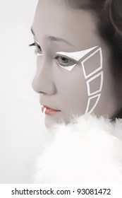 Portrait of a young beautiful woman with artistic makeup and white feathers