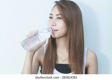 Portrait of young beautiful woman asia drinking water at summer and holding bottle