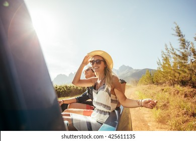 Portrait of a young beautiful woman in the back of truck with friends on a sunny day. Young people on a road trip.