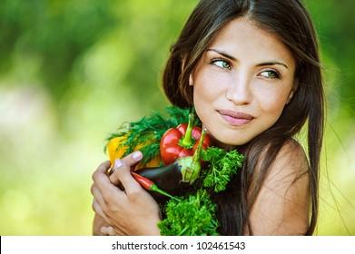 Porträt von jungen schönen Frauen mit nackten Schultern, die ein Gemüse halten - Petersilie, Pfeffer, Auberginen, auf grünem Hintergrund Sommernatur.