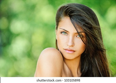 Portrait of young beautiful woman with bare shoulders , on green background summer nature.