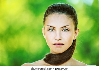 Portrait of young beautiful woman with bare shoulders, on green background summer nature.