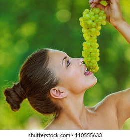 Portrait of young beautiful woman with bare shoulders holding grapes, on green background summer nature.