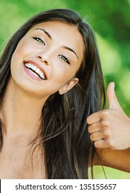 Portrait of young beautiful woman with bare shoulders happily raises his thumb up and smiling, on green background summer nature.
