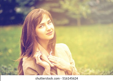 Portrait of a young beautiful woman in beige coat posing on a background of autumn park