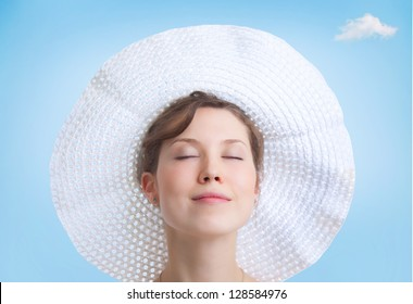 Portrait of young beautiful woman in big white hat
