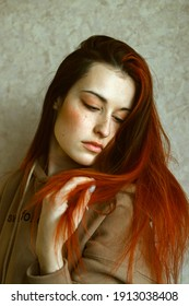 Portrait of a young beautiful woman with big eyes, freckles, who straightens her long red hair. She is in the room