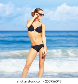 portrait of young beautiful woman in black bikini and sunglasses on blue