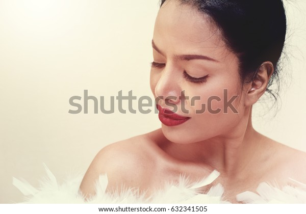 Portrait of young beautiful woman with black vintage hairdo and white feather boa