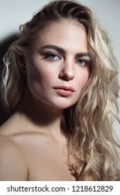 Portrait of young beautiful woman with blond curly messy hair