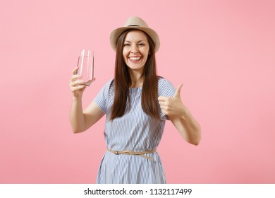 Portrait of young beautiful woman in blue dress, hat holding and drinking clear fresh pure water from glass isolated on pink background. Healthy lifestyle, people sincere emotions concept. Copy space
