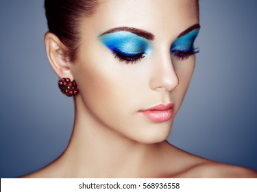 Portrait of young beautiful woman with blue makeup. Face Girl with earring close up. Fashion jewelry