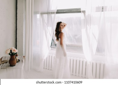 Portrait of a young beautiful woman. Bride in elegant classic wedding dress. Morning of the bride. Wedding preparations.