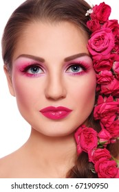 Portrait of young beautiful woman with bright make-up and pink roses in hair