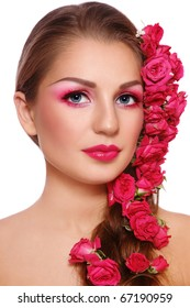 Portrait of young beautiful woman with bright make-up and roses in hair, on white background