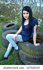 portrait of young beautiful woman with broken car aside