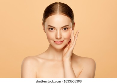 Portrait of young beautiful woman with brown eyes and glowing skin, isolated on beige background. Skincare concept
