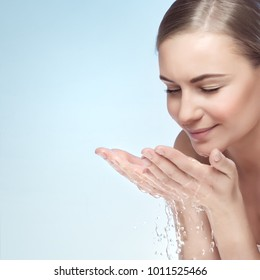 Portrait of a young beautiful woman cleaning her face by water, isolated on blue background, morning freshness, removing makeup, skin health and beauty care concept