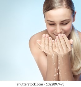 Portrait of a young beautiful woman cleaning her face with fresh water, morning freshness, removing makeup, skin care routine, health and beauty concept