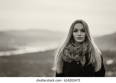 Portrait, the young, beautiful woman in a coat, against the background of a decline, twilight, soft focus. Black-and-white, effect of a film