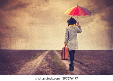 portrait of a young beautiful woman with colorful umbrella and brown suitcase standing on the road