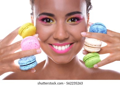 Portrait of young beautiful woman with colourful macaroons