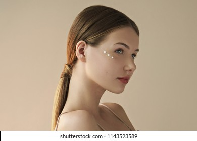 portrait of young beautiful woman with cream on her face on beige background