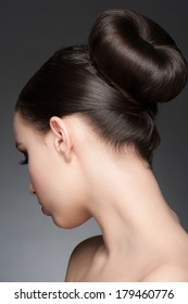 Portrait of young beautiful woman with creative elegant hairstyle, hair bun. Rear view