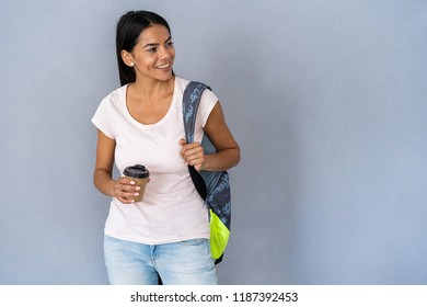 Portrait of a young beautiful woman with a cup of coffee. trendy latin student girl carrying backpack