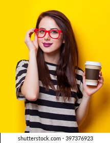 portrait of a young beautiful woman with cup of coffee standing on the yellow background