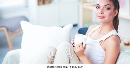 Portrait of young beautiful woman with a cup on sofa at home