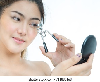 Portrait of young beautiful woman curling her eyelashes isolated on white, Close up of a beautiful asian woman using eyelash curler while looking in makeup mirror at home over white background.