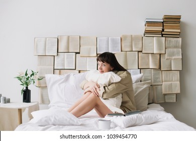 Portrait of a young beautiful woman with dark hair having breakfast in bed in the morning at home. Beautiful young brunette with a cup of coffee in the bedroom. Good morning. Lifestyle.