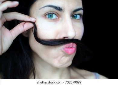 Portrait of a young beautiful woman with dark hair holding a strand of her hair over her upper lip. The concept of the problem of removing excess hair on the face of women. Funny face.