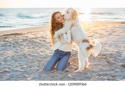 Portrait of a young beautiful woman with dog on the beach.
