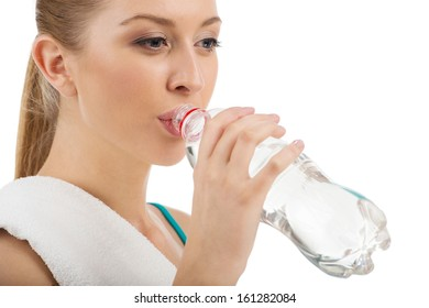 Portrait of young beautiful woman drinking water after training. Isolated on white