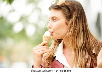 Portrait of young beautiful woman eating tasty vanilla icecream in sugar cone when walking outdoors