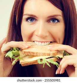 Portrait of young beautiful woman eating sandwich with cheese