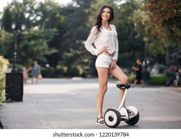 Portrait of a young beautiful woman with electric mini segway hover board scooter. Self balancing scooter board