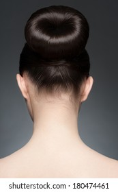Portrait of young beautiful woman with elegant hairstyle, hair bun. Rear view
