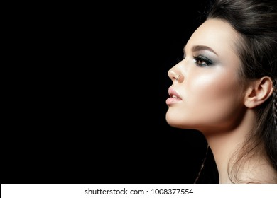 Portrait of young beautiful woman with evening make up. Model posing over black background. Silver smokey eyes. Classic makeup concept. Studio shot. Copy space