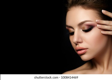 Portrait of young beautiful woman with evening make up touching her face over black background. Multicolored smokey eyes. Luxury skincare and modern fashion makeup concept. Studio shot. Copy space
