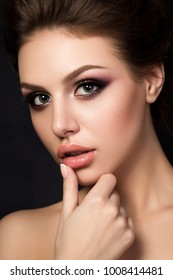 Portrait of young beautiful woman with evening make up touching her lips over black background. Red and gold multicolored smokey eyes. Luxury skincare and modern fashion makeup concept. Studio shot.