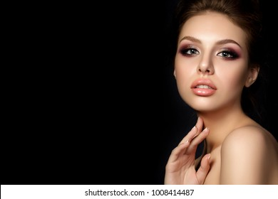 Portrait of young beautiful woman with evening make up touching her neck over black background. Multicolored smokey eyes. Luxury skincare and modern fashion makeup concept. Studio shot. Copy space