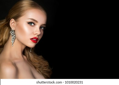 Portrait of young beautiful woman with evening make up. Model posing over dark background. Red lips and eyeliner. Classic makeup concept. Studio shot. Copy space