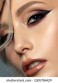 Portrait of young beautiful woman with evening make up. Modern fashion eyeliner wing. Studio shot. Extreme closeup, partial face view