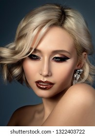 Portrait of young beautiful woman with evening make up. Modern fashion eyeliner wing and glitter on her lips. Studio shot.